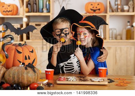 Hugging brother and sister in Halloween costumes eating treats