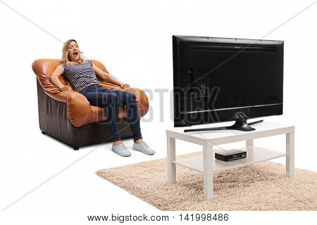 Scared blond woman watching a horror movie on TV seated on an armchair isolated on white background
