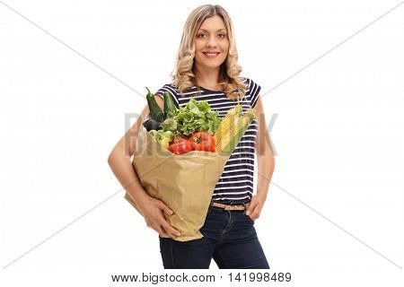 Attractive young woman carrying a bag of groceries and looking at the camera isolated on white background