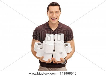 Smiling young man holding a pile of toilet paper rolls isolated on white background