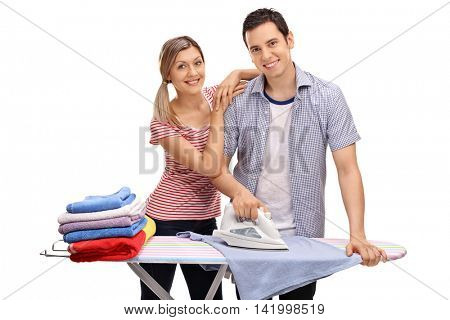 Happy young couple ironing together and looking at the camera isolated on white background