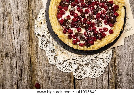 Homemade rustic pie with berries filling. Raspberries, ricotta and chocolate pie on a rustic wooden background.  Summer baking.  Selective focus