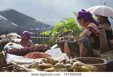 LAO CAI, VIETNAM - OCT 17, 2015: Hmong tribe people selling chili pepper and other agriculture products at Can Cau flea market. Flea market is very popular as one kind of small business in Vietnam.