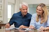 Mature couple doing family finances at home. Senior couple discussing home economics sitting at tabl poster