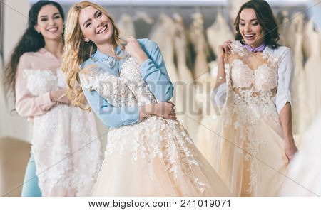 poster of Young Smiling Bride And Bridesmaids Choosing Dresses In Wedding Salon