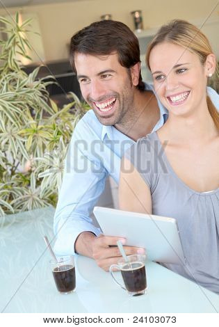 Happy young couple at home using electronic tablet