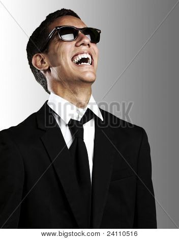 portrait of young business man with suit and sunglasses laughing against a grey background
