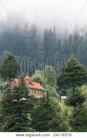 House in mountains covered by clouds