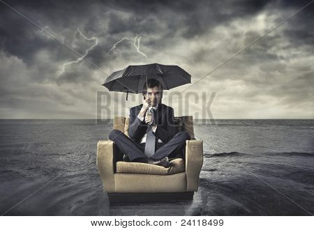 Businessman sitting under an umbrella on an armchair in the middle of the sea
