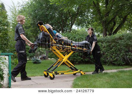 Female emergency medical team transporting senior patient on stretcher