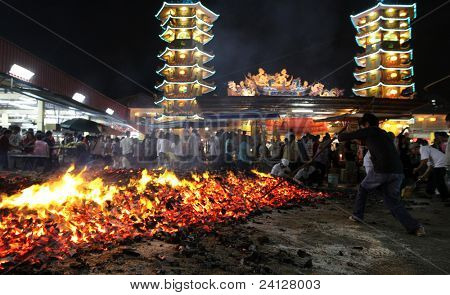 AMPANG, MALAYSIA – OCT 05: A devotee prods the fire pit to collect charcoal blessed after the fire-walk at the Lam Thian Kiong Temple during the '9 Emperor Gods' Festival on October 05 2011 in Ampang, Malaysia.