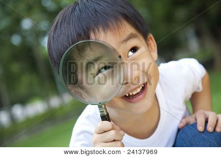 asian boy holding magnifier at green park