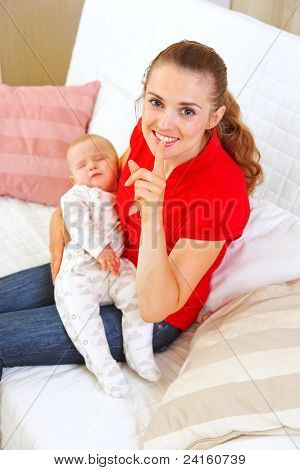Happy Mother Holding Sleeping Baby And Showing Shhh Gesture