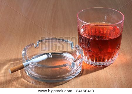 Color photo of a glass of whiskey and ashtray