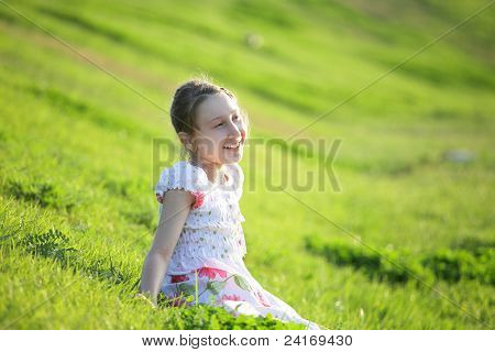 Girl sits on a grass