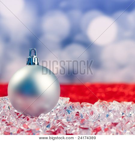 Christmas silver bauble on ice cubes with blue lights bokeh background