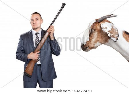 Businessman With Gun Looking At Goat