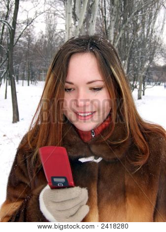 Girl In The Winter In Park With Phone In A Hand