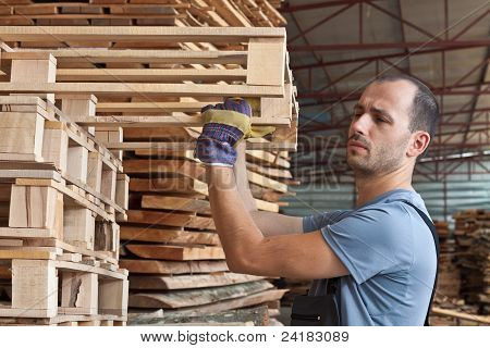Man Arranging Pallets, Horizontal Shot
