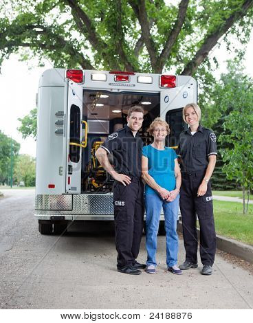 Portrait of patient with ambulance staff outside vehicle