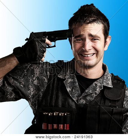 portrait of young soldier trying to suicide against a blue background