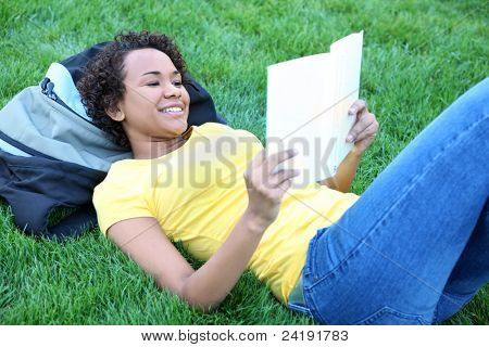 A pretty african american woman reading book in park