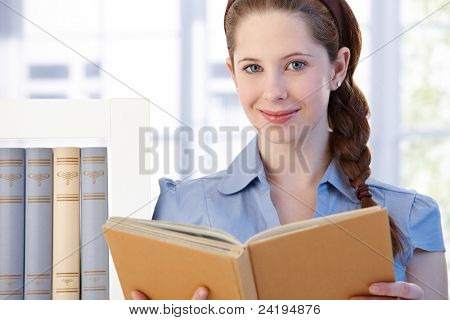 Portrait of attractive young woman standing in living room at home, reading a book, smiling.?