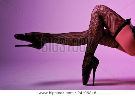 Sexy female legs in fishnet stockings and extreme fetish ballet shoes, studio shot