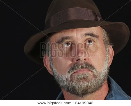 A Bearded Man In A Fedora Looks Up