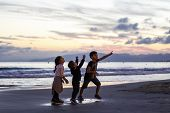 Silhouette Of Three Kids Playing On The Beach At Sunset. Conceptual Scene. poster