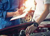 Car Owner With Car Mechanic Check Car Repair Machine In The Garage. poster