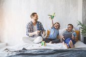 Full Length Outgoing Dad Playing With Cheerful Kids On Bed. Elder Brother Watching At Electronic Tab poster
