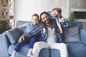 Portrait Of Outgoing Dad And Happy Kids Locating On Cozy Couch In Living Room. Positive Family Conce poster