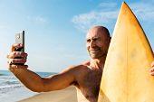 Man holding surfboard taking selfie