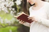 Cropped Young Tender Beautiful Woman In Light Casual Clothes Reading Interesting Book Standing In Ci poster