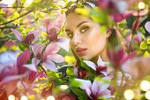 Beauty young woman enjoying nature in spring spring magnolia flowers. Beautiful brunette girl in Gar poster