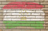 Flag Of Tajikistan On Grunge Brick Wall Painted With Chalk