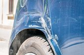 Damaged Car. Blue Scratched Car With Damaged Paint In Crash Accident On The Street Or Parking Lot In poster