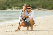 Happy Handsome Father And Son Embracing On Tropical Beach poster