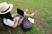 Young Hipster Woman Using Laptop While Sitting In Park With Bag And Blank Notebook. poster