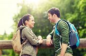 travel, hiking, backpacking, tourism and people concept - smiling couple with backpacks in nature lo poster