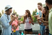 Group Of Young People Sitting Around And Eating Pizza. Friends Partying And Eating Pizza. poster
