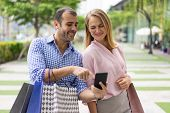 Happy Stylish Couple Using Mobile App For Shopping. Smiling Man And Woman With Shopping Bags Walking poster