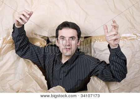 young man making a large hole in paper