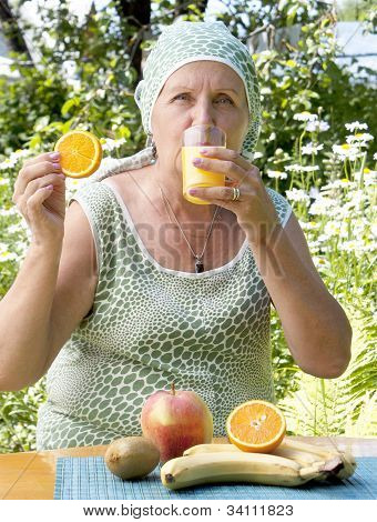 The happy adult woman drinks fresh orange juice