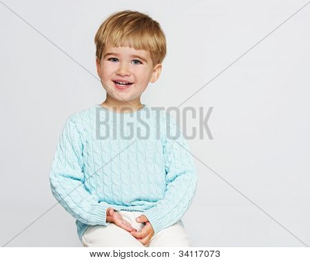Smiling baby boy in blue pullover