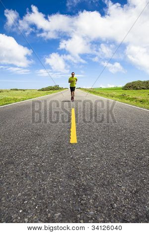 young man running on the empty road at summertime