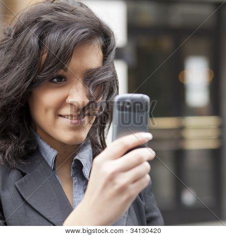 Junge Frau mit Handy fotografiert