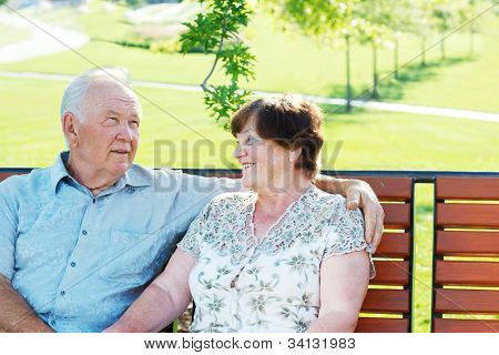 Cheerful grandparents sitting in park