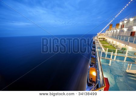cruise ship floats at night, long exposure